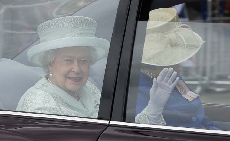Britain's Queen Elizabeth II waves from the back of her State Limousine accompanied by a Lady in Waiting as she is driven from St. Paul's Cathedral to lunch after service to celebrate the Queen's Diamond Jubilee in London on June 5, 2012. (Miguel Medina/AFP/Getty Images)