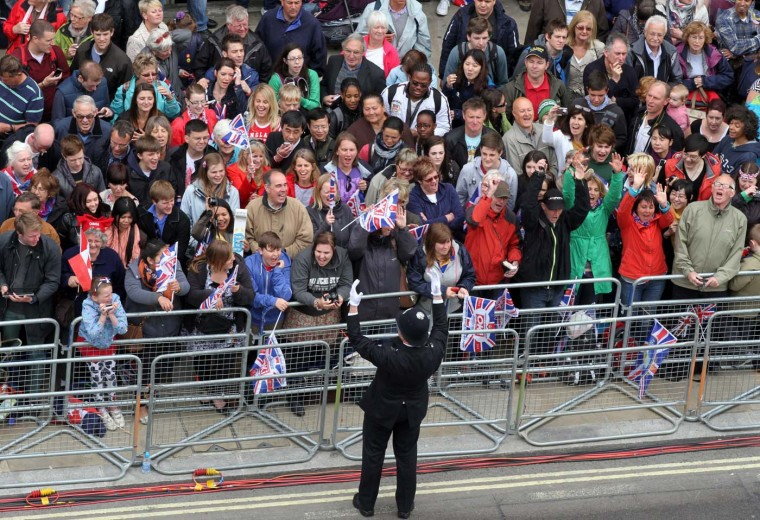 A policeman rallies the crowds as they line up to watch the carriage procession carrying Britain's royal family during the Queen's Diamond Jubilee in London, on June 5, 2012. (Elizabeth Dalziel/AFP/Getty Images)