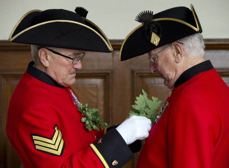 Chelsea Pensioners, British veteren soldiers, fix their oak leaf sprigs during the annual Founder's Day Parade at the Royal Chelsea Hospital in London (Miguel Medina/Getty Images)
