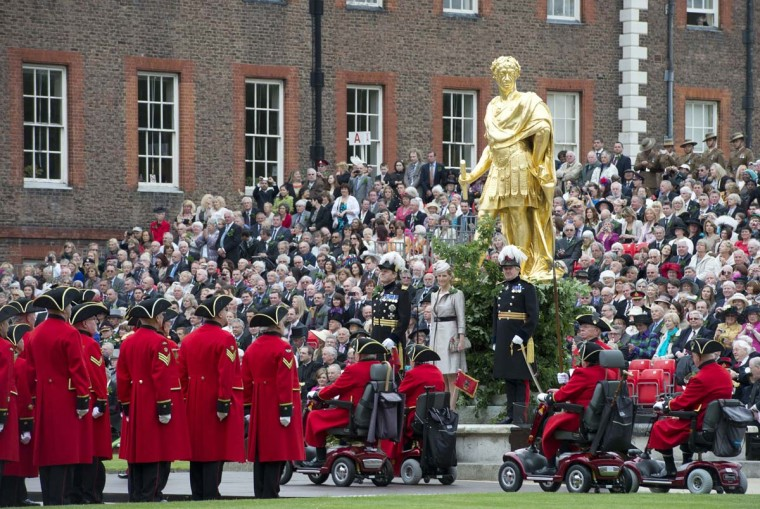Chelsea Pensioners, all British veteren soldiers, stand to attention for inspection as others drive mobility scooters past Sophie, Countess of Wessex, standing at the base of a statue of King Charles II during the annual Founder's Day Parade at the Royal Chelsea Hospital. (Miguel Medina/Getty Images)