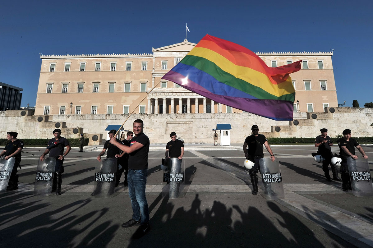 """Athens: A participant of the Gay Pride event waves a rainbow flag by police protecting the Greek parliament on June 9, 2012. Some 1000 people took part at a march organized by Greece's gay and lesbian community, with the main slogan """"love me, its for free."""" (Louisa Goulia-Maki, Aris Messinis/AFP/Getty Images)"""