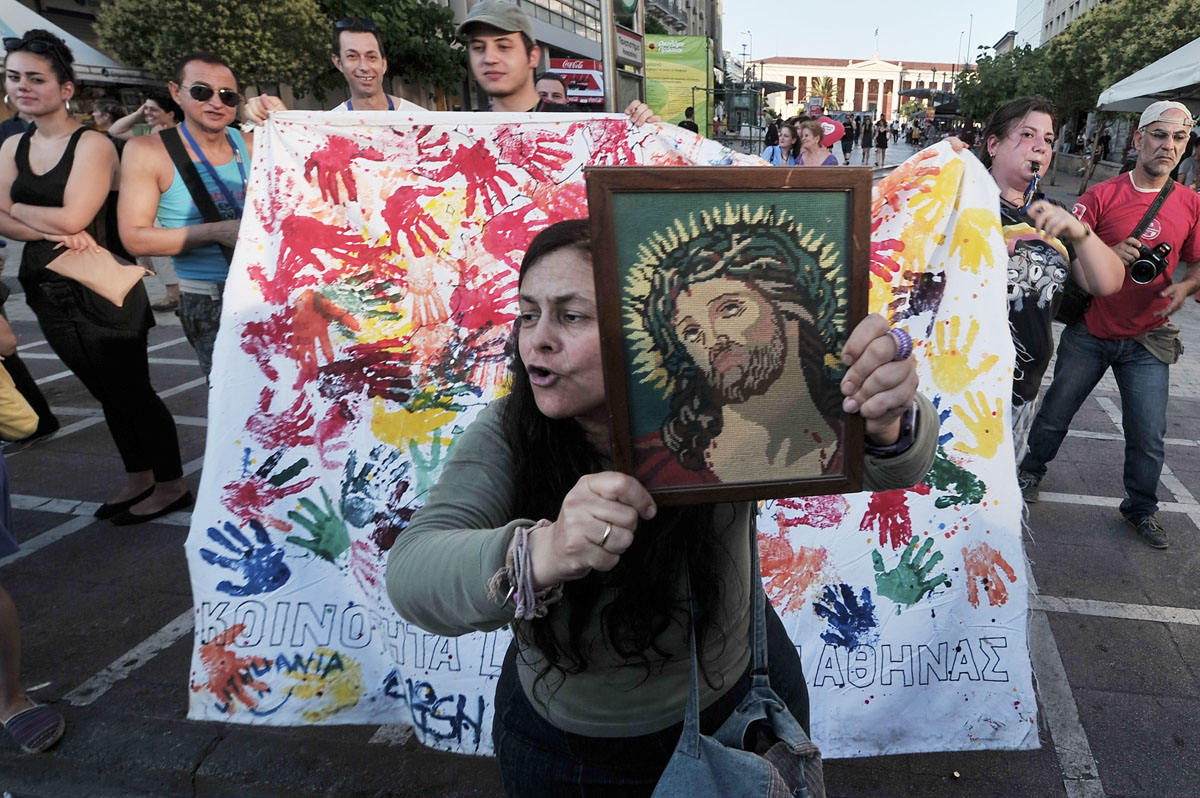 """Athens: A Christian woman displays a holy icon during the gay pride parade on June 9, 2012. Some 1000 people took part at a march organized by Greece's gay and lesbian community, with the main slogan """"love me, its for free."""" (Louisa Goulia-Maki, Aris Messinis/AFP/Getty Images)"""