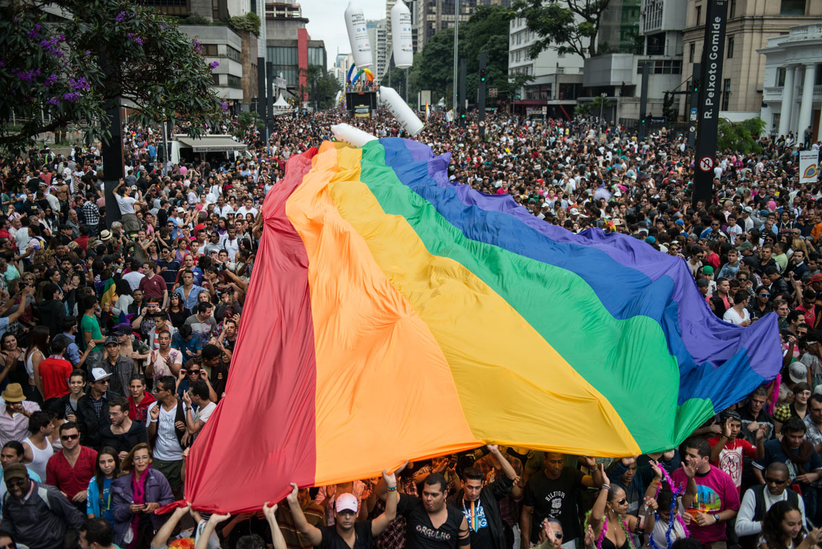 """Sao Paulo: A huge rainbow flag is unfolded during the annual gay pride parade on June 10, 2012. About 3 million people were expected to take part in the parade under the 2012 theme """"Homophobia has cure."""" (Yasuyoshi Chiba/AFP/Getty Images)"""