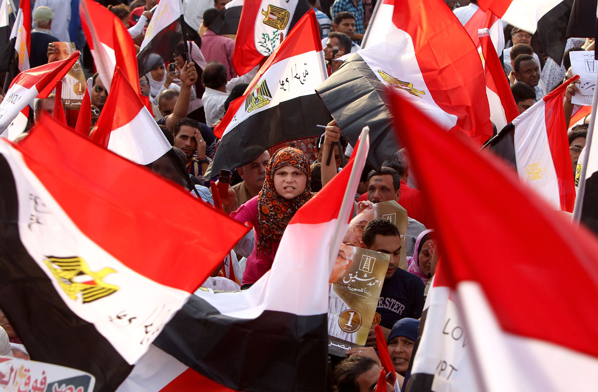 June 23, 2012; Hundreds of supporters of presidential candidate Ahmed Shafiq, the last prime minister of ousted leader Hosni Mubarak, hold up the national flag as they demonstrate in Nasr city on the outskirts of Cairo. Tensions soared in Egypt a day before the result of a divisive presidential election and as the Muslim Brotherhood sparred with the ruling generals over what it sees as a military power grab. (Marwan Naamani/AFP/Getty Images)