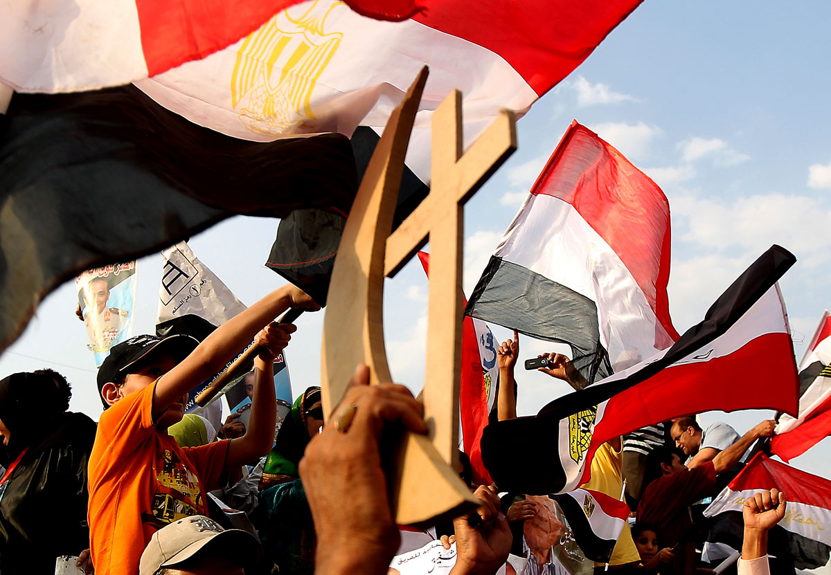 June 23, 2012: A supporter of presidential candidate Ahmed Shafiq, the last prime minister of ousted leader Hosni Mubarak, holds up a wooden Christian cross and Muslim crescent as he and others demonstrate in Nasr city on the outskirts of Cairo. Tensions soared in Egypt a day before the result of a divisive presidential election and as the Muslim Brotherhood sparred with the ruling generals over what it sees as a military power grab. (Marwan Naamani/AFP/Getty Images)