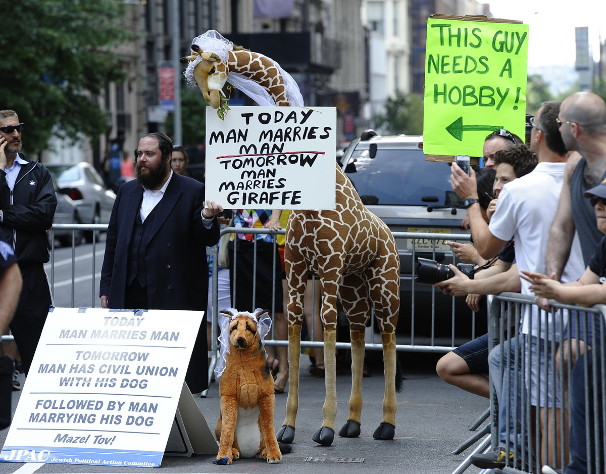 New York: A protestor holds signs against same-sex marriage during the 2012 New York Gay Pride parade on June 24, 2012. The 43rd-annual parade with more than 500,000 people is part of Gay Pride week. (Timothy A. Clary/AFP/Getty Images)