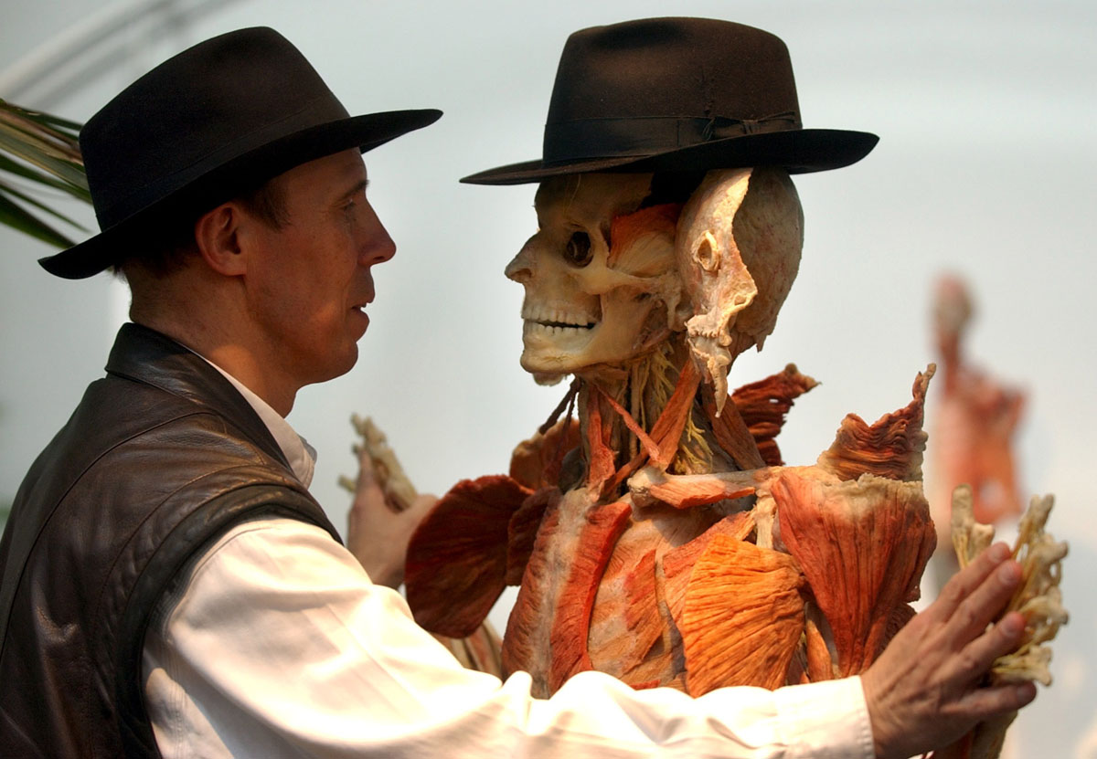 "July 12, 2002: Gunther von Hagens, creator of the exhibition ""Body Worlds,"" stands with one of nine new body plastinates at the Atlantis Gallery in east London. The anatomical exhibition of real human bodies is set to become the most visited exhibition in London ever. (Matthew Fearn/AFP Photo)"