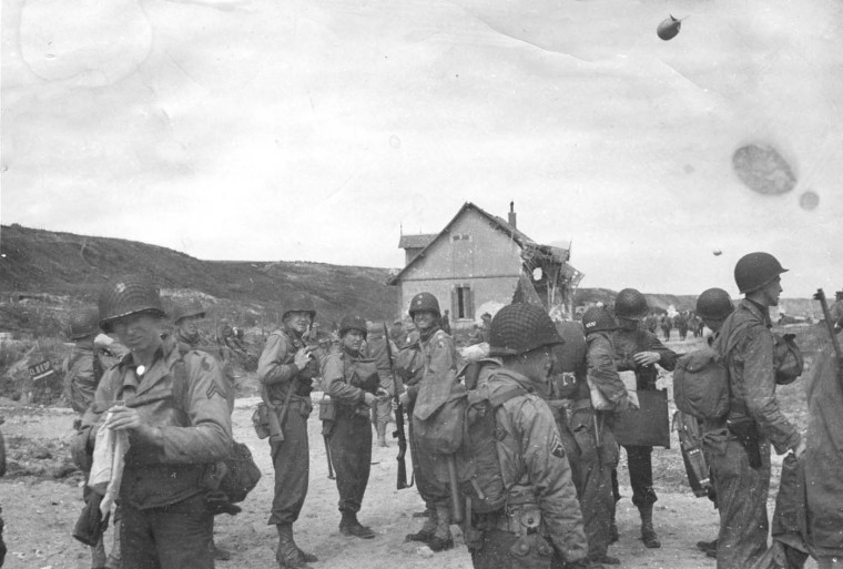 Scene on beach near Vierville on June 8, 1944 when support troops landed. Four men facing camera center of picture are left to right: Capt. Henry Hubbard, Farmville, Va., Lieut. Paul Clapper, Cumberland, Maj. Thomas Dukehart, Baltimore, and Capt. Artnold Ellis, Richmond, Va. (Holbrook Bradley/Baltimore Sun)