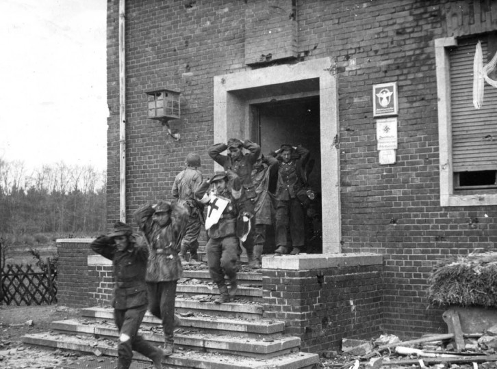Germans surrender and shown leaving doorway under guard Blue and Grey riflemen who captured them April 1945. (Holbrook Bradley/Baltimore Sun)