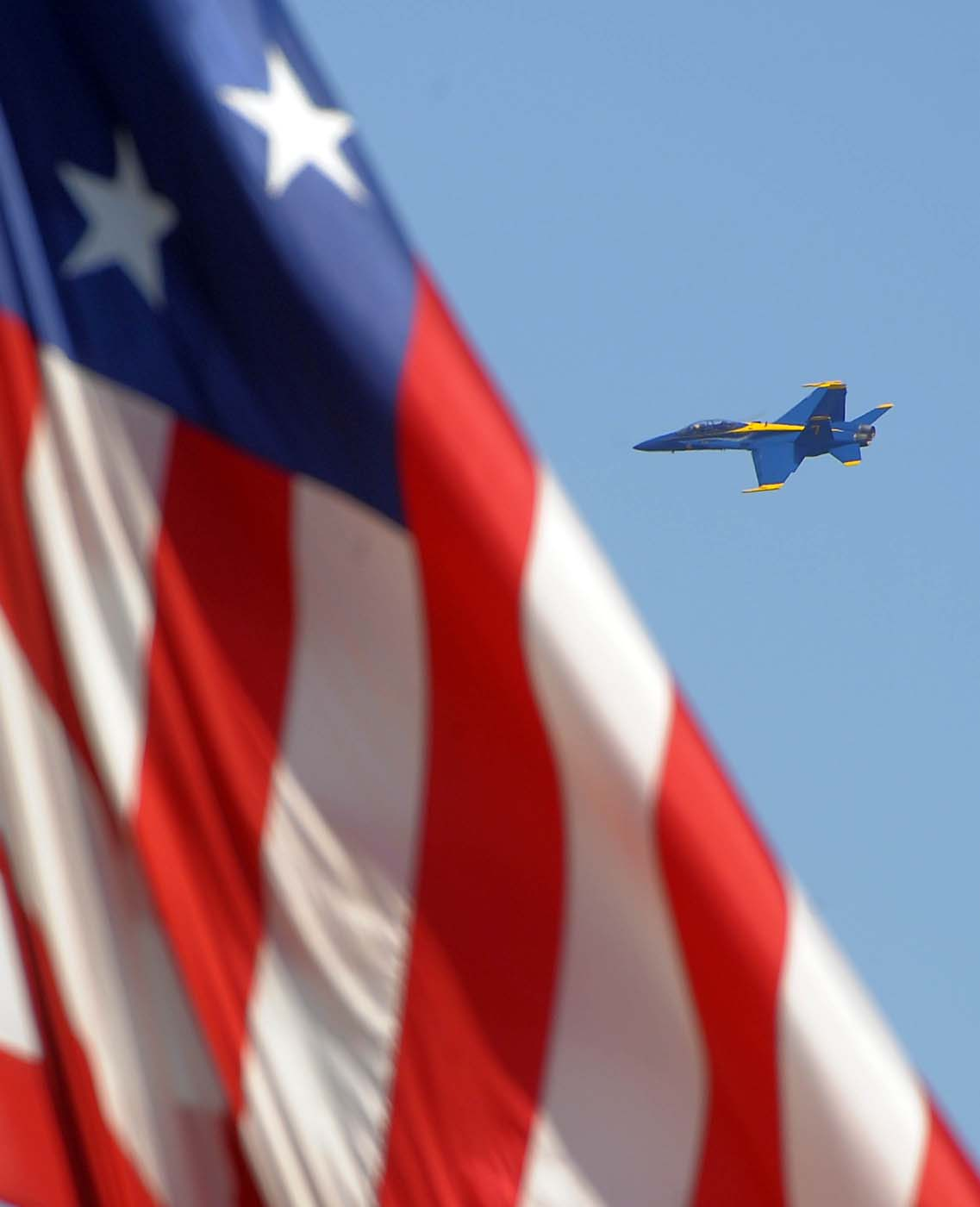 A Blue Angel flies behind the replica 15-star, 15-stripe U.S. flag of Fort McHenry, participating in the air show during the weekend-long Star Spangled Sailabration Saturday, Jun 16, 2012. (Karl Merton Ferron/Baltimore Sun)