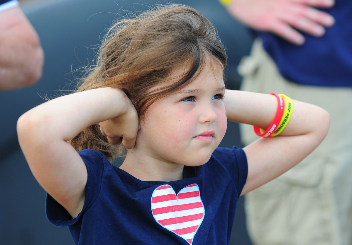 Six-year-old Perry Stevenson holds her ears during Friday practice for the air show. (Gene Sweeney Jr./Sun Photographer)