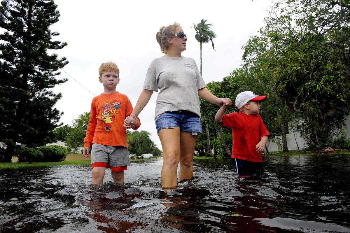 Angela Kelly, along with her sons Ethan, 3, and Alex, 6, walk through their neighborhood inspecting the flooding as high winds and rain associated with Tropical Storm Debby continue to affect the area in St. Petersburg, Florida. (Brian Blanco/Reuters photo)