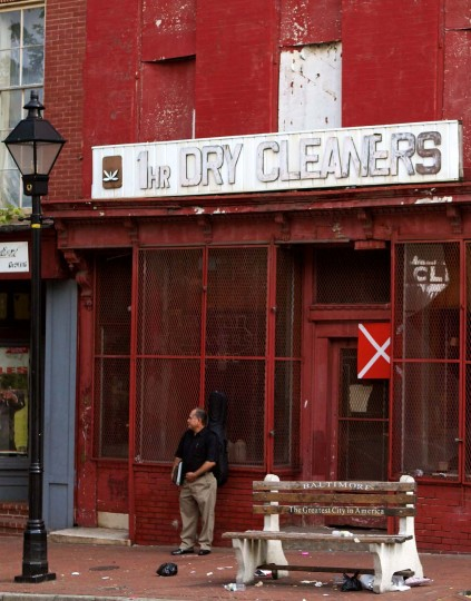 "A man stands in front a business with the sign ""1 Hr Dry Cleaners"" on Baltimore Street. (Will Cocks/Will Cocks Photography)"