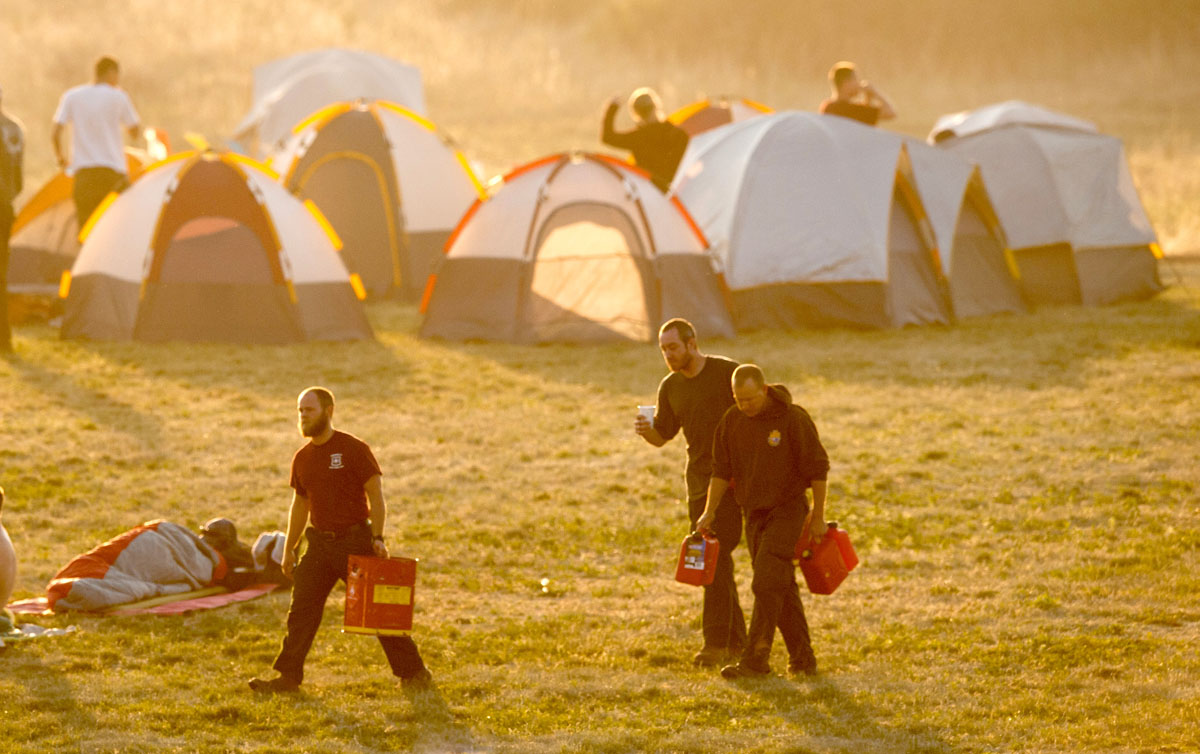 JUNE 26: Firefighters stir from their tents at a firefighter camp at Holmes Middle School early Tuesday morning, June 26, 2012, to begin work on the fourth day of the Waldo Canyon Fire burning west of Colorado Springs, Colorado. (Mark Reis/Colorado Springs Gazette/MCT)
