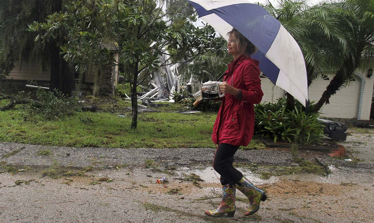 Kathy Bee walks by a collapsed pool enclosure in Winter Park, Florida, carrying a freshly-brewed pot of coffee to a neighbor that lost power after a squall line from Tropical Storm Debby caused damage to the area. (Red Huber/Orlando Sentinel/)