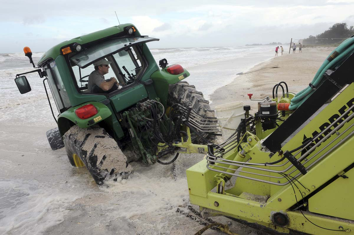 Mark Taylor, an employee with Manatee County Parks and Recreation, became stuck while cleaning the sand on Manatee Public Beach after Tropical Storm Debby, passed over Manatee County, Florida. (Tiffany Tompkins-Condie/Bradenton Herald)