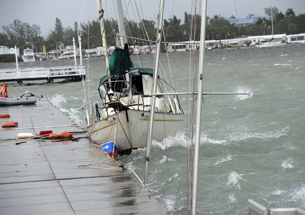 A sailboat that broke free from its anchor during Tropical Storm Debby batters against the Bridge Street Pier next to a sinking boat in Manatee County, Florida. (Tiffany Tompkins-Condie/Bradenton Herald)