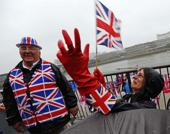 Samantha Malcolm waves a Union Flag as she waits with her friend Mike Reakes in the rain for the start of the river pageant to celebrate Queen Elizabeth's Diamond Jubilee in London June 3, 2012. (Luke MacGregor/Reuters)