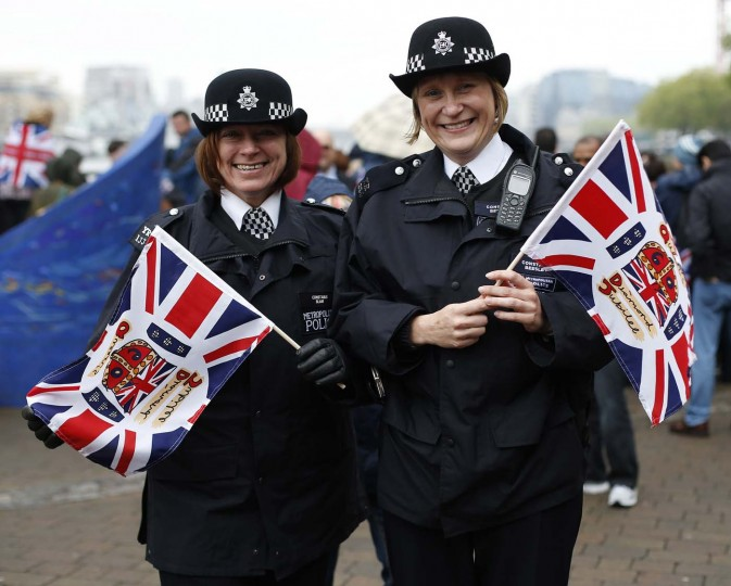 Police constables Tracey Blair (L) and Clare Beesley pose for a photograph with Union flags near Tower Bridge in London June 3, 2012. (Eddie Keogh/Reuters)