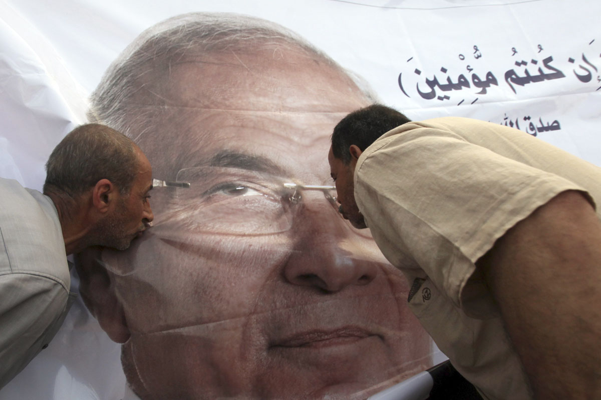 June 23, 2012: Supporters of former prime minister and presidential candidate Ahmed Shafik kiss his poster during a protest against the Muslim Brotherhood's presidential candidate Mohamed Morsy in front of the military parade stand at Nasr City in Cairo. (Amr Abdallah Dalsh/Reuters)