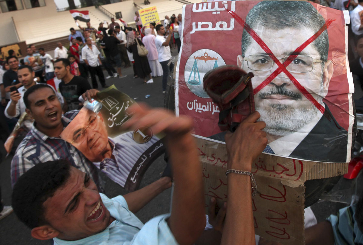 June 23, 2012: Supporters of former prime minister and current presidential candidate Ahmed Shafik hit a defaced poster of the Muslim Brotherhood's presidential candidate Mohamed Morsy with shoes during a rally in support of the Supreme Council for the Armed Forces (SCAF) at Nasr City in Cairo. (Amr Abdallah Dalsh/Reuters)