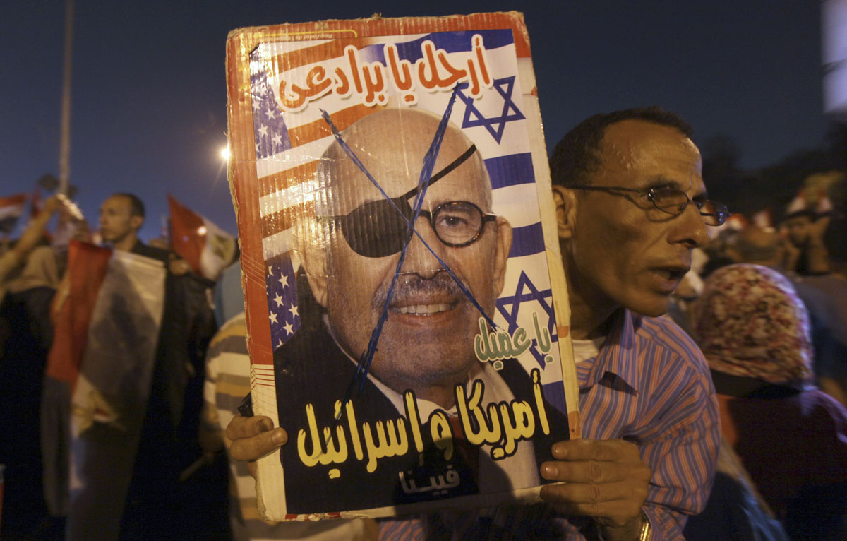 June 23, 2012: A supporter of former prime minister and current presidential candidate Ahmed Shafik holds a defaced picture of Egyptian political figure Mohamed ElBaradei and former UN nuclear watchdog chief during a protest against the Muslim Brotherhood's presidential candidate Mohamed Morsy as they cheer for the Supreme Council for the Armed Forces (SCAF) in Cairo. (Amr Abdallah Dalsh/Reuters)