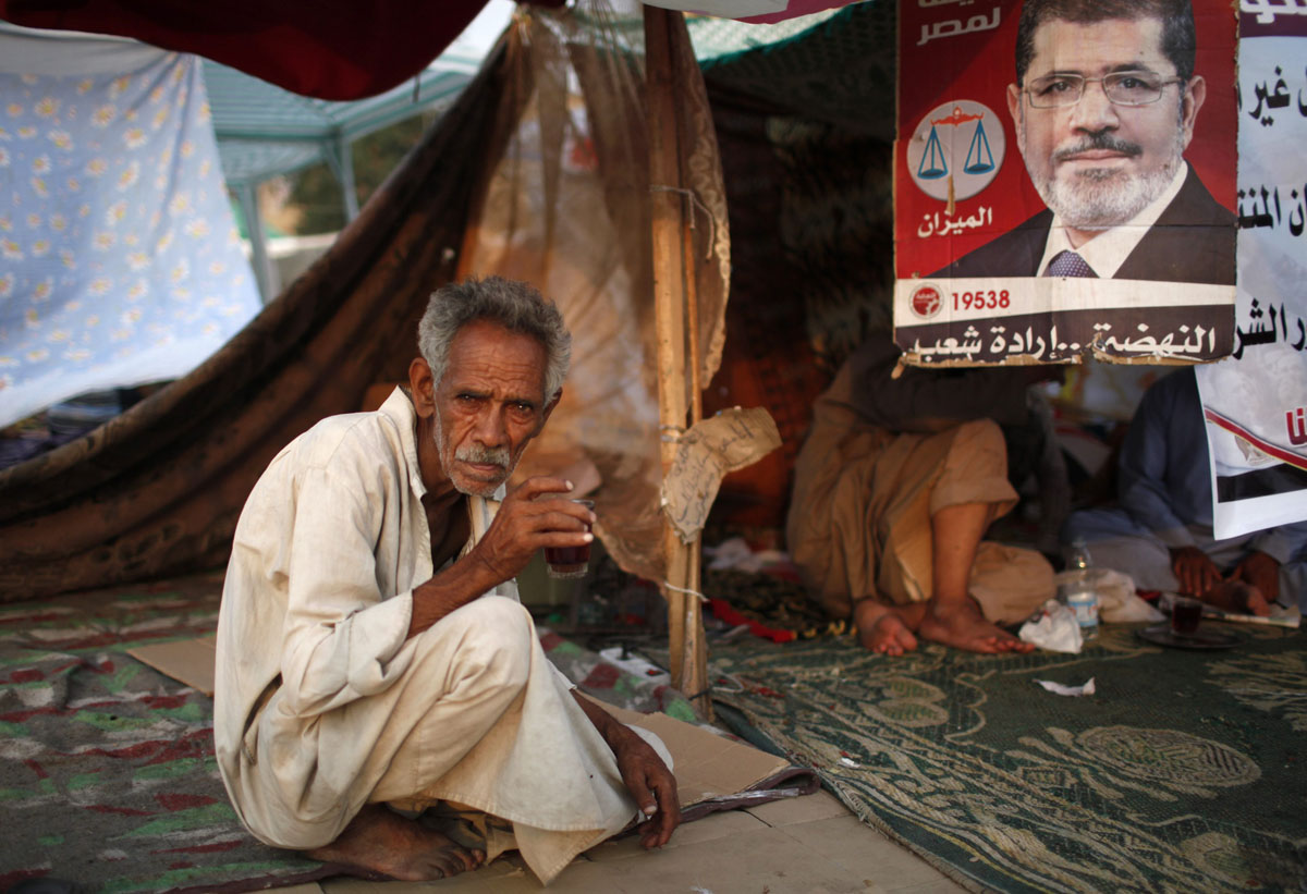 June 23, 2012: A supporter of Muslim Brotherhood's presidential candidate Mohamed Morsy drinks tea during a sit-in protest against the delay of the Egyptian presidential results and Supreme Council for the Armed Forces (SCAF) at Tahrir Square in Cairo. (Ahmed Jadallah/Reuters)