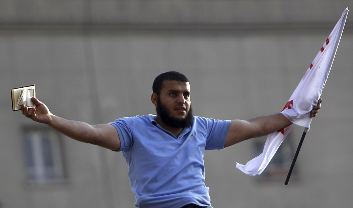 "June 24, 2012: A supporter of Muslim Brotherhood's president-elect Mohamed Morsy holds a Koran and a Salafi flag as he celebrates Morsy's victory at the election at Tahrir Square in Cairo. Morsy pledged on Sunday to be a president for all Egyptians in a televised address after the Islamist was declared the winner of last weekend's election - an event he called a ""historic moment."" (Amr Abdallah Dalsh/Reuters)"