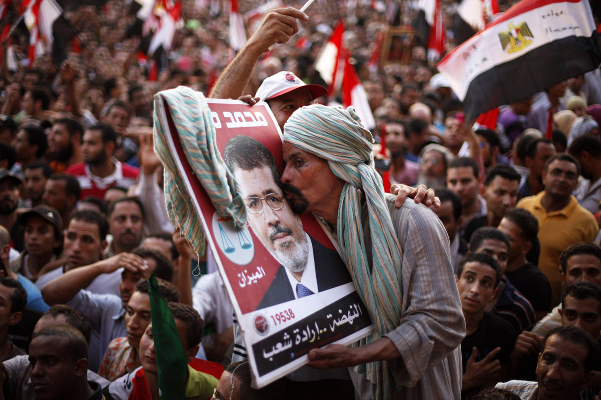 June 24, 2012: A supporter of Muslim Brotherhood's presidential candidate Mohamed Morsy kisses his picture during a celebration of his victory at the election at Tahrir Square in Cairo. (Suhaib Salem/Reuters)
