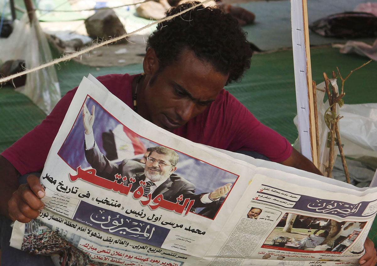 June 25, 2012: A protester reads a newspaper bearing a photo of President-elect Mohamed Mursi (L) during a sit in at Tahrir square in Cairo. The protesters want to keep up pressure on the ruling military council to hand full powers to the newly elected president, Mursi, of the Muslim Brotherhood. (Asmaa Waguih/Reuters)