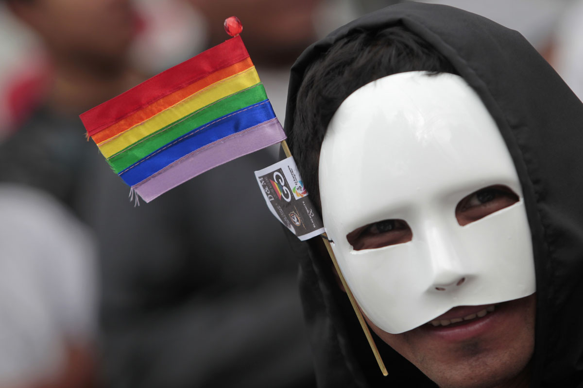 Guatemala City: A masked member of the Lesbian, Gay, Bisexual and Transgender (LGBT) community, bearing the rainbow flag, looks on during the XII Parade of Sexual Diversity June 23, 2012. (Jorge Dan Lopez/Reuters)