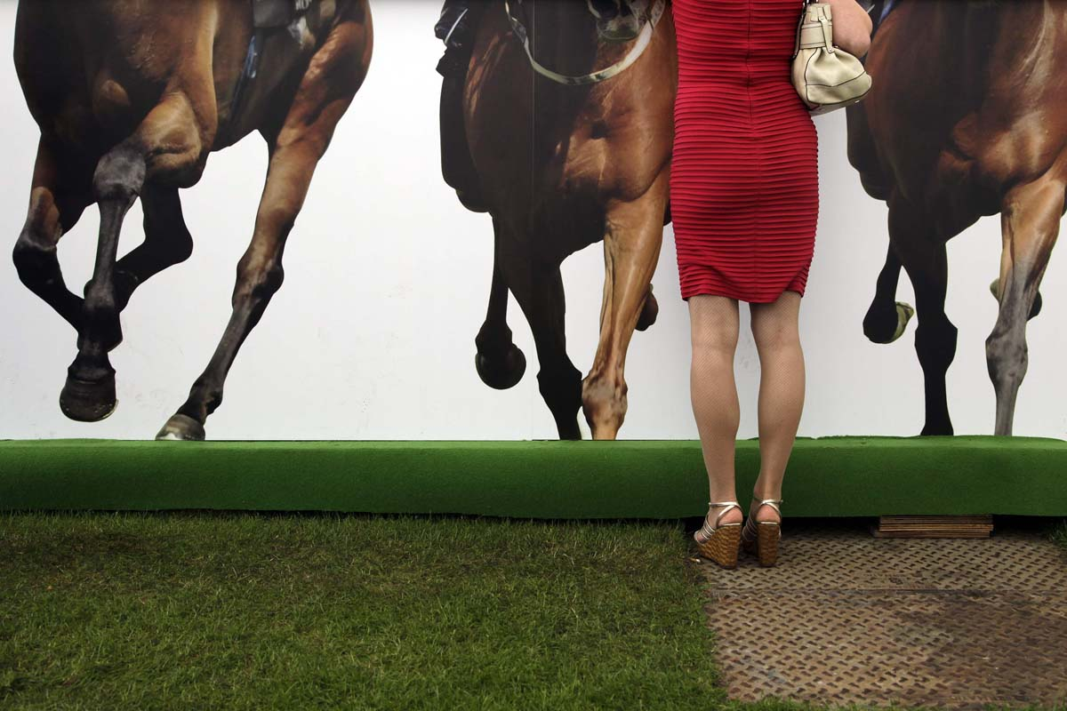 A racegoer stands on a bar on Ladies Day, the third day of racing at the Royal Ascot, southwest of London. (Stefan Wermuth/Reuters photo)