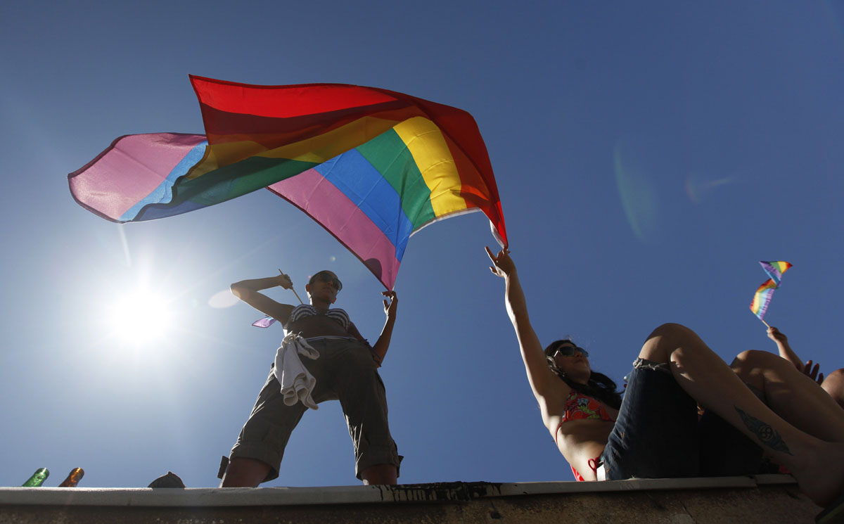 Tel Aviv: Women hold a rainbow flag from a roof-top during an annual Gay Pride parade June 8, 2012. Revelers paraded in the streets of Israel's free-wheeling city of Tel Aviv, which has become a Mediterranean hotspot for gay tourism, ending their celebration with a party on the beach. (Amir Cohen/Reuters)