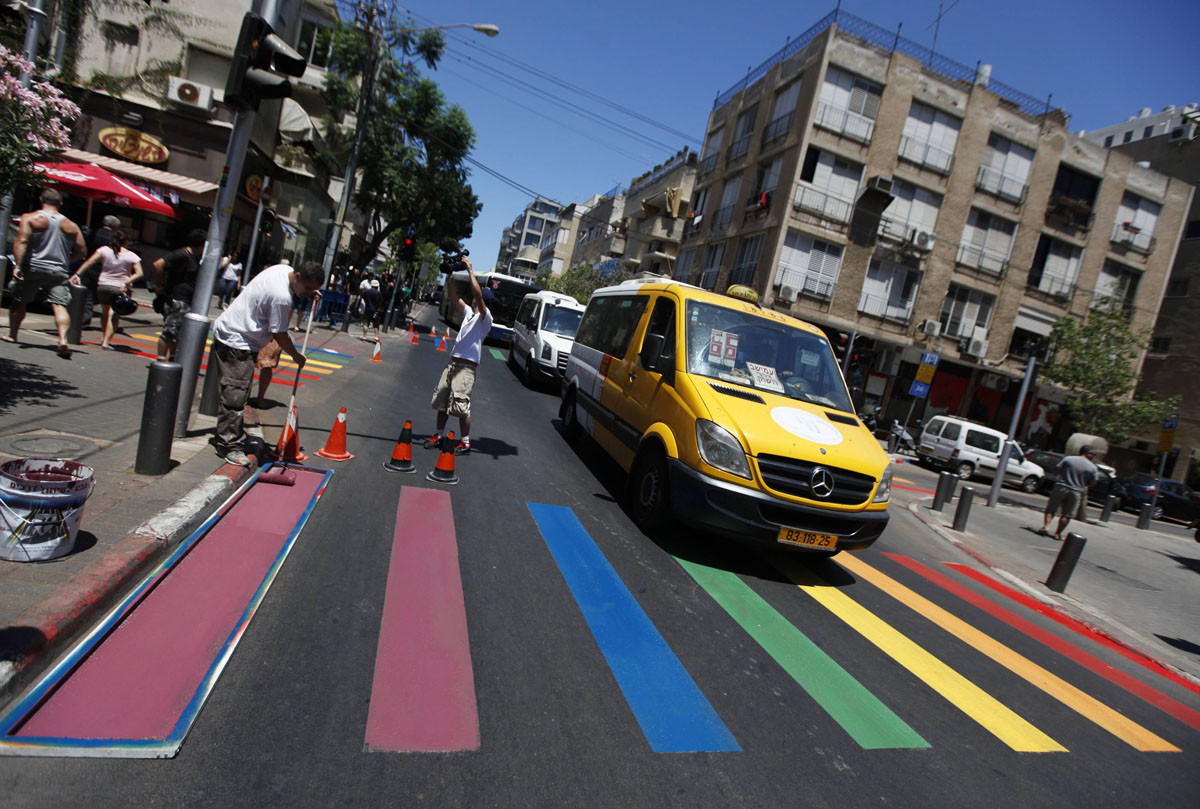 Tel Aviv: A mini-bus drives past as municipality workers paint a pedestrian crossing in the colours of a rainbow flag before the annual Gay Pride parade June 8, 2012. (Amir Cohen/Reuters)