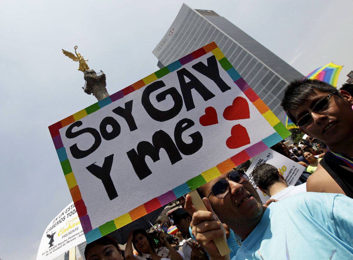 """Mexico City: A participant holds up a placard during the Gay Pride Parade, in front of the Angel of Independence column June 2, 2012. Thousand of gays, lesbians, transsexuals and supporters took part in the parade. The placard reads, """"I'm gay and I love."""" (Henry Romero/Reuters)"""