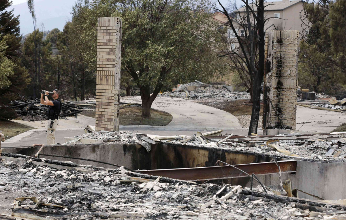 JUNE 29: A U.S. Secret Service counter sniper watches out as U.S. President Barack Obama walks around fire damaged homes in the Mountain Shadow neighborhood in Colorado Springs, Colorado June 29, 2012. Obama declared the areas earlier today as a federal disaster area releasing federal funds to help fight the blazes. (Larry Downing/Reuters)