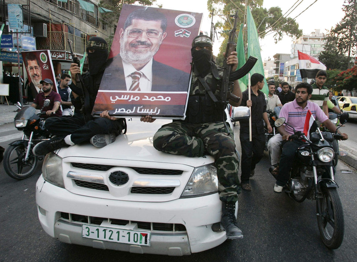 June 24, 2012: Hamas militants hold a poster depicting Mohamed Morsy of the Muslim Brotherhood as they celebrate in the street in Gaza City after he was declared Egypt's first democratic president. Morsy's win was hailed by Hamas, the Islamist group governing Gaza and which is locked in a power-struggle with the West Bank-based, U.S.-backed Palestinian Authority of President Mahmoud Abbas. (Mohammed Salem/Reuters)