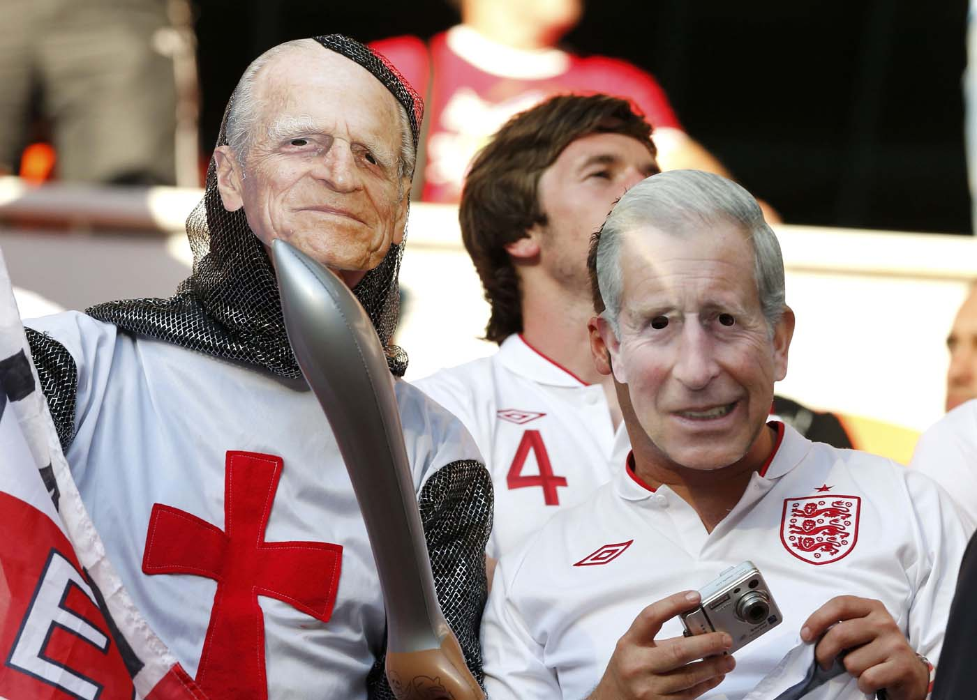 England's fans wear Prince Charles (R) and Prince Philipp masks as they cheer before Group D Euro 2012 soccer match against France at the Donbass Arena in Donetsk June 11, 2012. (Yves Herman/Reuters)