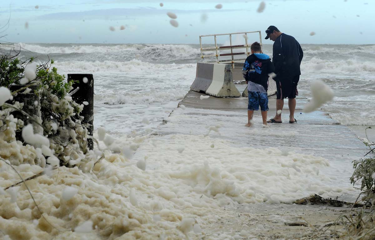 Mike Cook, of Bradenton, and his son Justin, 7, walk out to check out the waves on the Gulf of Mexico as storm surge and high winds associated with Tropical Storm Debby batter Bradenton Beach, Florida. (Brian Blanco/Reuters photo)