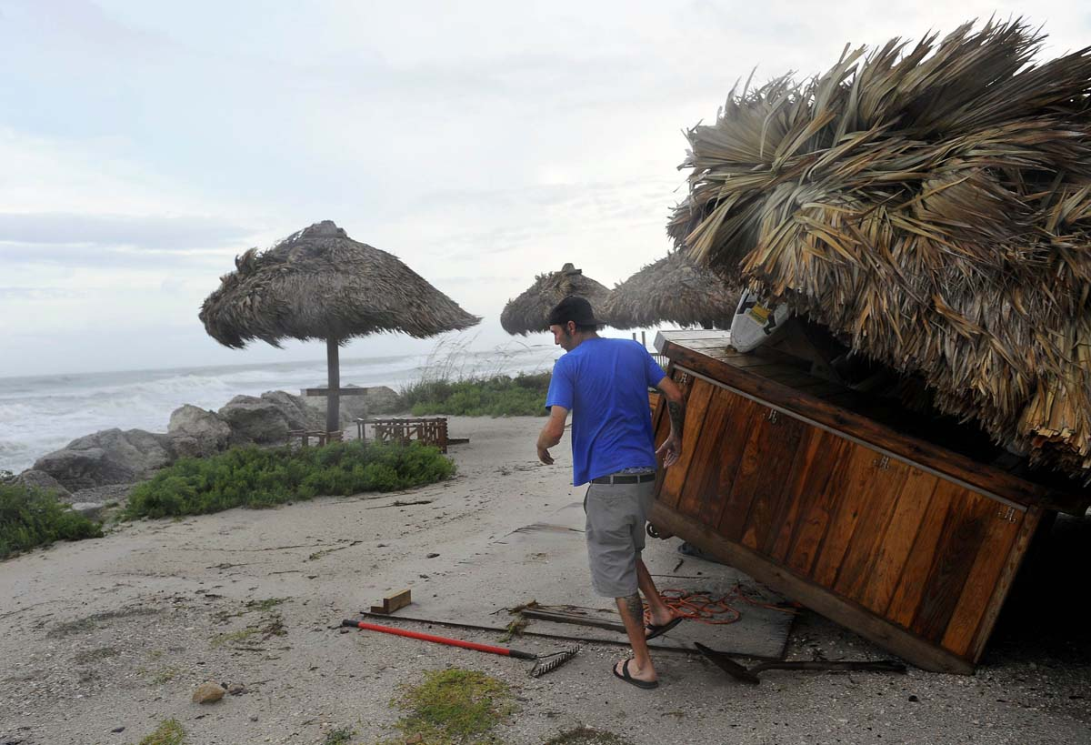 Manager Jeff Higgins, of the Gulf Drive Cafe, inspects damage to his restaurant as a storm surge and high winds associated with Tropical Storm Debby batter Bradenton Beach, Florida. (Brian Blanco/Reuters photo)