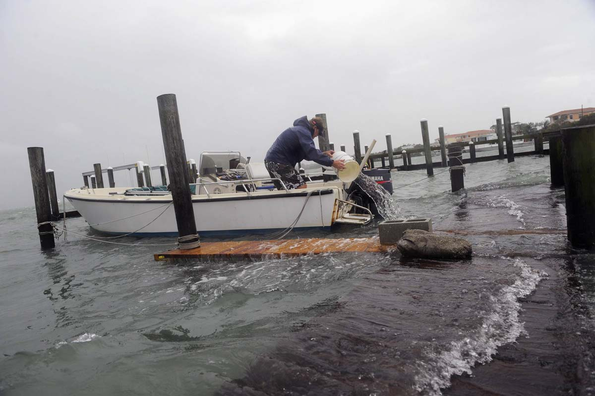 Reed Frost, from Bradenton Beach, attempts to bail out his flooded boat as a storm surge and high winds from Tropical Storm Debby batter Bradenton Beach. (Brian Blanco/Reuters photo)