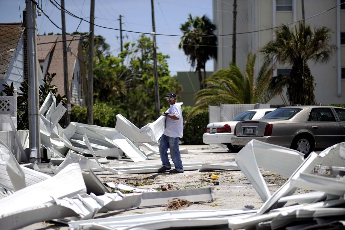 A worker begins the process of removing material torn from nearby buildings in Pass-A-Grille Beach, damaged by what residents describe as a tornado, as high winds and storm surge associated with Tropical Storm Debby continue to affect the area in Florida. (Brian Blanco/Reuters photo)
