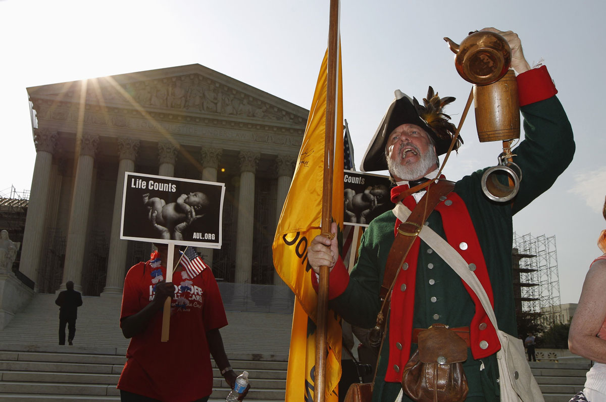 June 28, 2012: Tea Party supporter William Temple holds up a tea pot as he shouts against President Barack Obama's 2010 healthcare overhaul outside the Supreme Court in Washington, June 28, 2012. The Supreme Court is set to deliver on Thursday its ruling on President Barack Obama's 2010 healthcare overhaul, his signature domestic policy achievement, in a historic case that could hand him a huge triumph or a stinging rebuke just over four months before he seeks re-election. (Jason Reed/Reuters)