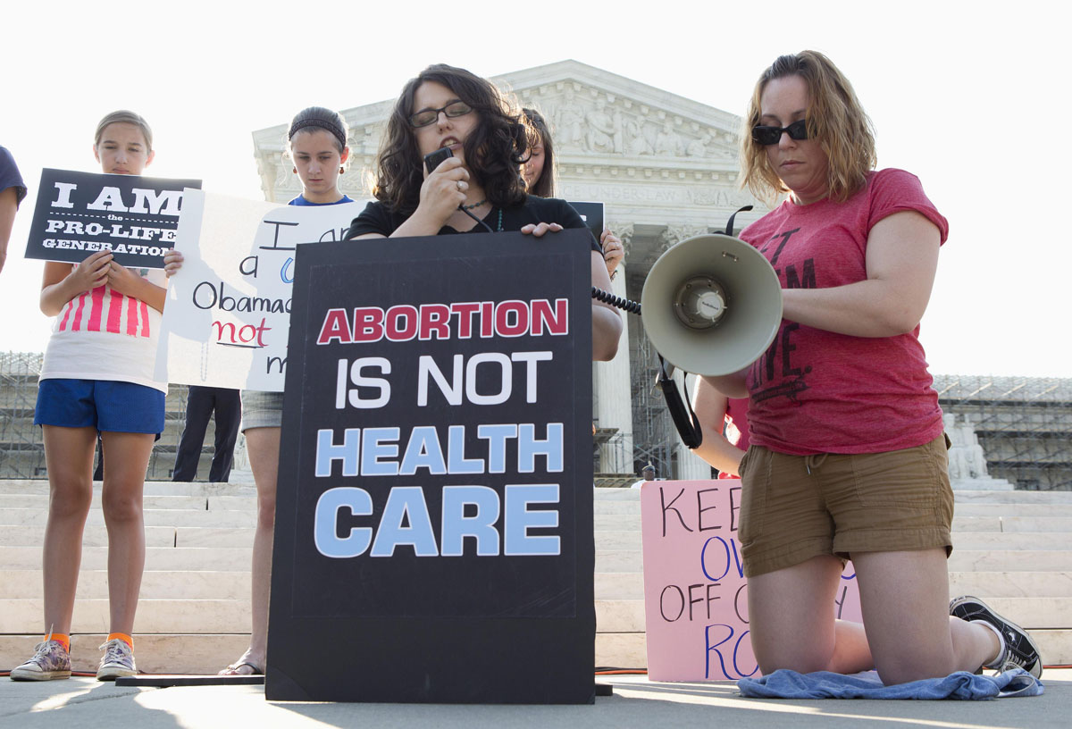 June 28, 2012: Detractors of the Affordable Healthcare Act gather in front of the Supreme Court before the court's announcement of the legality of the law in Washington on June 28, 2012. The U.S. Supreme Court is set to deliver on Thursday its ruling on President Barack Obama's 2010 healthcare overhaul, his signature domestic policy achievement, in a historic case that could hand him a huge triumph or a stinging rebuke just over four months before he seeks re-election. (Joshua Roberts/Reuters)
