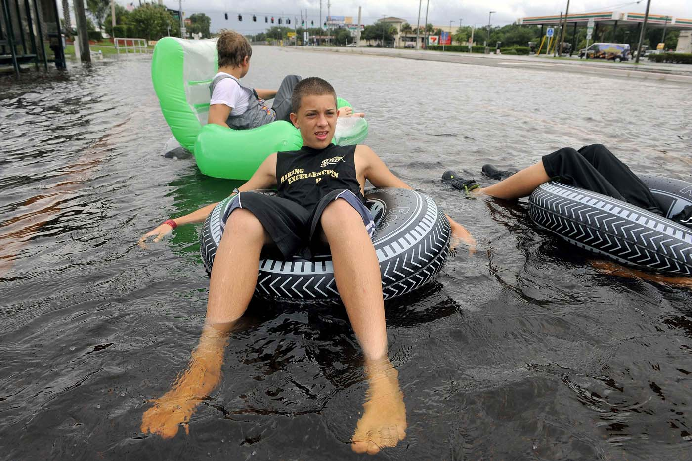Matt Smeaton (C), 14, joins friends as they float down a closed six-lane road as floodwater associated with Tropical Storm Debby rises around them in New Port Richey, Florida, June 26, 2012. (Brian Blanco/Reuters)