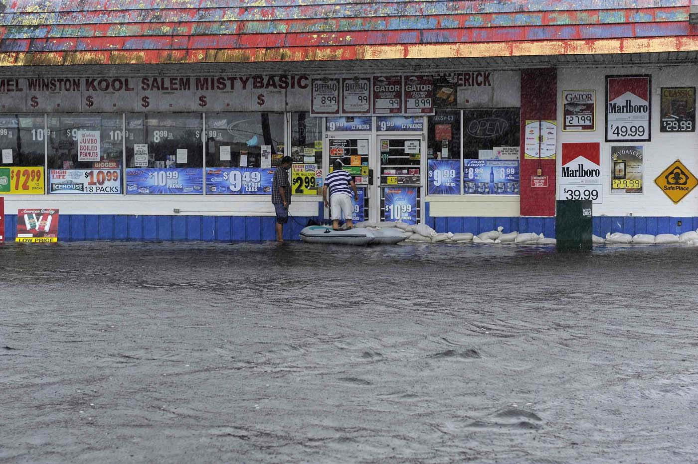 With the rain falling around them, business owners use a small boat to check on the status of the water inside their store as floodwater associated with Tropical Storm Debby rises in New Port Richey, Florida, June 26, 2012. (Brian Blanco/Reuters)