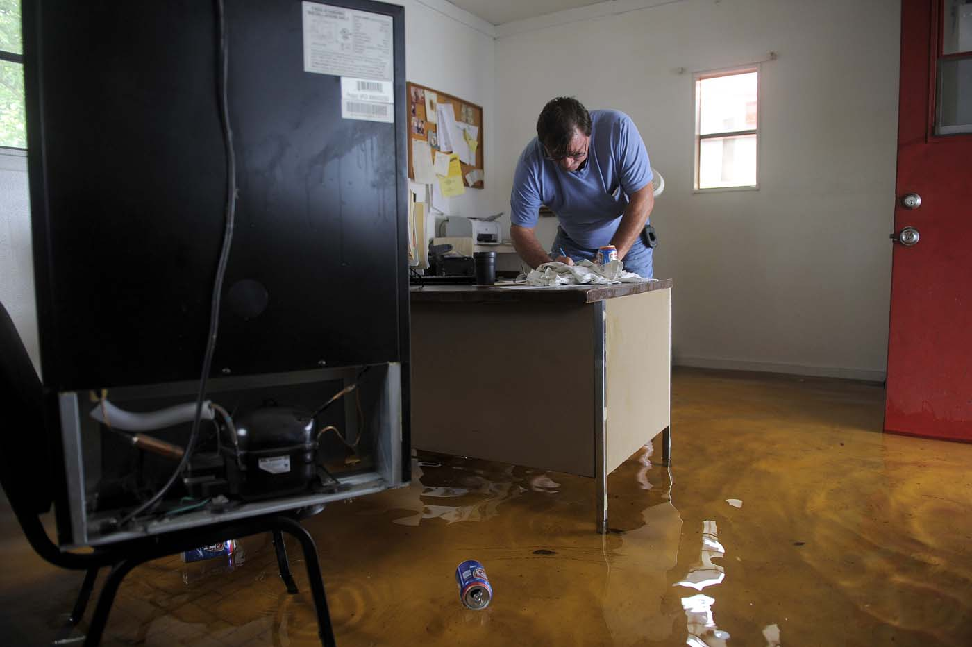 Tony Kiriwas leaves a note in the flooded office of his auto sales shop as floodwater associated with Tropical Storm Debby rises around him in New Port Richey, Florida, June 26, 2012. (Brian Blanco/Reuters)