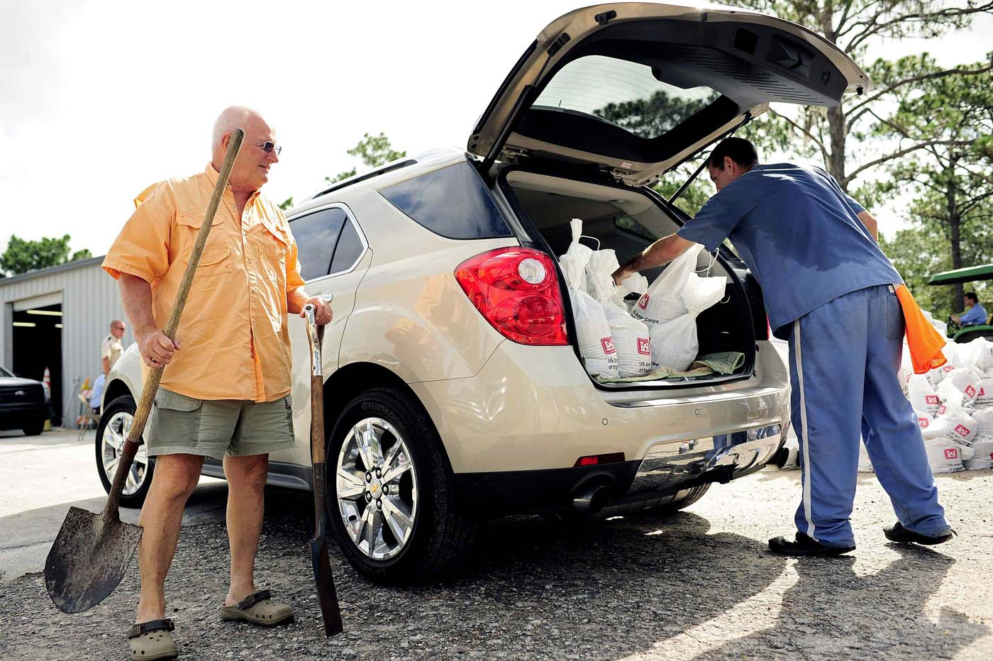 Bob Darr (L) pulls out his shovels to make room in his trunk, allowing an inmate from the Florida Department of Corrections to load sandbags into his car as he prepares to fight back the rising water associated with Tropical Storm Debby in Homosassa, Florida, June 26, 2012. (Brian Blanco/Reuters)