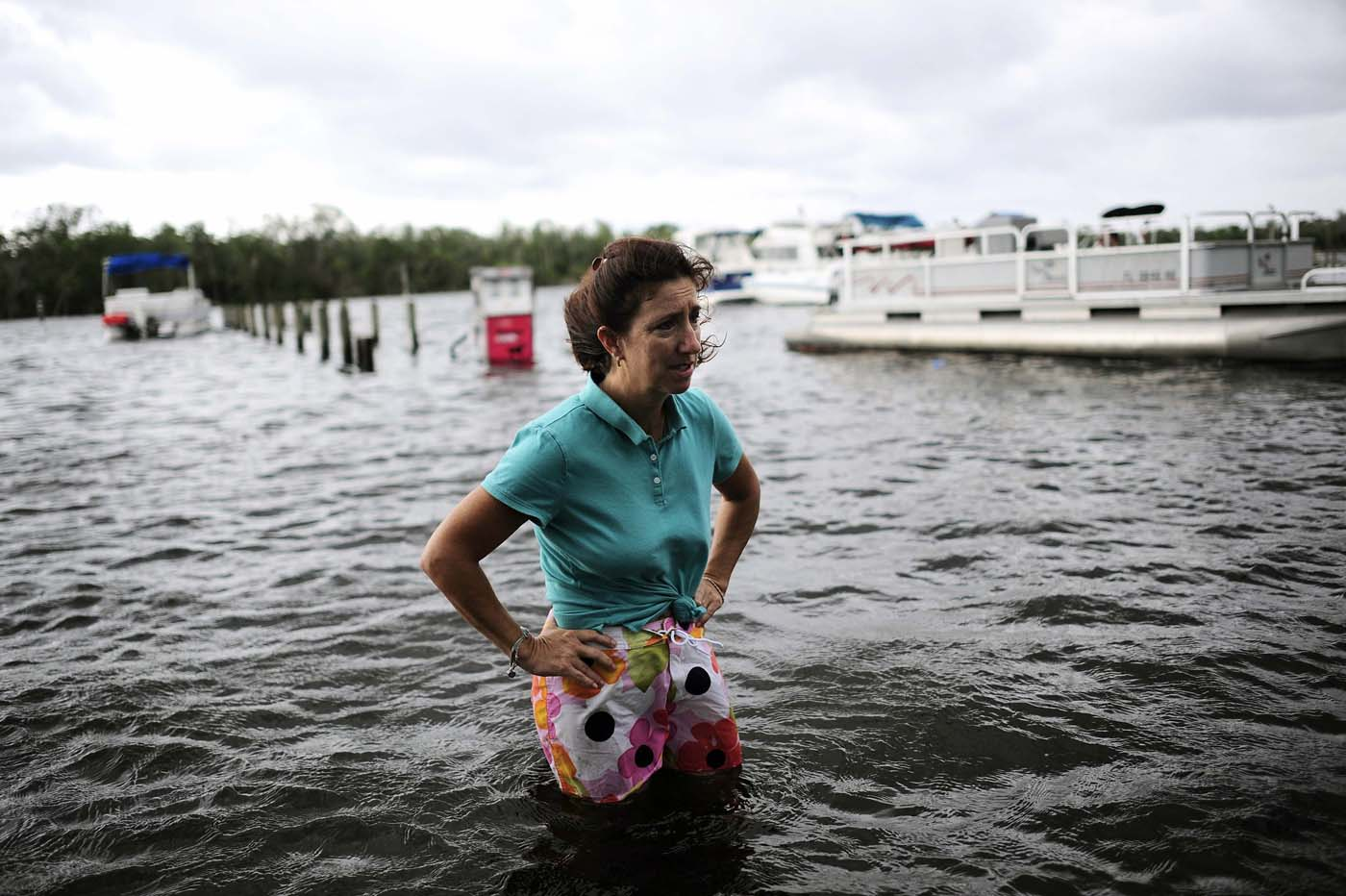Doreen Mylin, owner of the Magic Manatee Marina, pauses to inspect the damage as the water associated with Tropical Storm Debby rises and floods her business in Homosassa, Florida, June 26, 2012. (Brian Blanco/Reuters)