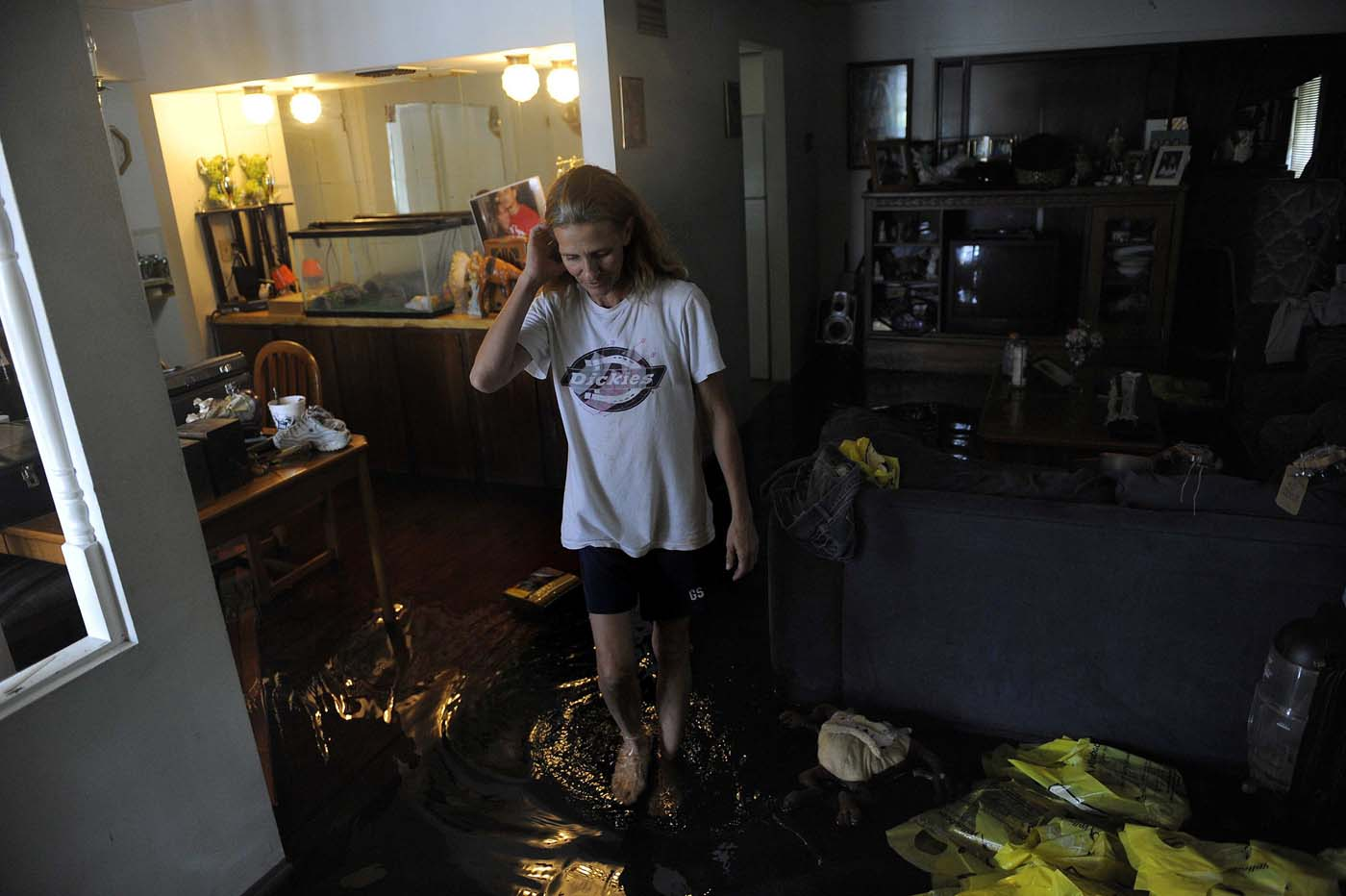 Refusing to evacuate despite over a foot of water inside her home, Georgia Brown inspects the damage in her living room caused by floodwater associated with Tropical Storm Debby in New Port Richey, Florida, June 26, 2012. (Brian Blanco/Reuters)
